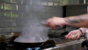 Кашевар конца поднимающий вверх в ресторане кухни жаря мясо с открытым огнем сток-видео