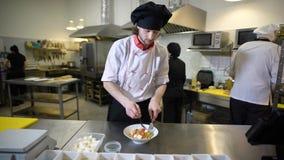 Кашевар, который одет в белых рисберме и крышке, элиты ресторан подготавливает vegetable салат, человека кладет сыр сток-видео