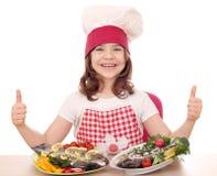 Кашевар маленькой девочки с форелью на плите и больших пальцах руки вверх Стоковое Фото