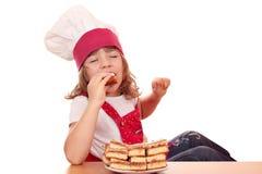 Кашевар маленькой девочки ест торт яблока Стоковая Фотография