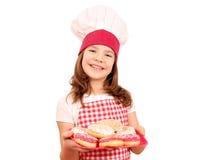 кашевар маленькой девочки с сладостными donuts на плите Стоковые Изображения