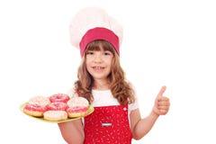 Кашевар маленькой девочки с donuts и большим пальцем руки вверх Стоковые Изображения