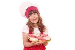 Кашевар маленькой девочки с donuts на плите Стоковое Изображение