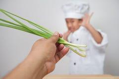 Кашевар маленькой девочки, шеф-повар детей испуганный овощей Стоковые Фотографии RF