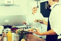 Кашевар молодой женщины давая салат к официантке Стоковое Изображение