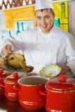 кашевар наводит форму ложки супа плиты Стоковая Фотография RF