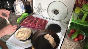 Кашевар окунает части мяса в бэттер, после этого в крошки Около сковороды зажарена первая часть мяса сток-видео