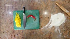 Кашевар отрезает перцы горячего chili на деревянной доске, пряную еду, еды с овощами, вегетарианской едой Взгляд сверху Стоковое Изображение RF