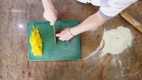 Кашевар отрезает перцы горячего chili на деревянной доске, пряную еду, еды с овощами, вегетарианской едой Взгляд сверху Стоковые Фотографии RF