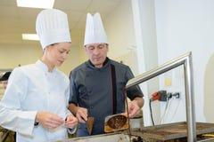 Кашевар печенья жизнерадостных молодых шеф-поваров профессиональный на работе Стоковая Фотография