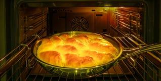 Кашевар печет пироги с яблоками на праздник в печи стоковые фото