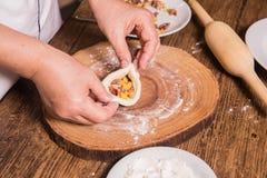 Кашевар подготавливает полумануфактурные тесто и мясо стоковое изображение