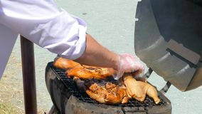 Кашевар раскрывает барбекю и поворачивает цыпленка, проверяет степень готовности сток-видео