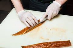 Кашевар режет угря с ножом на белой прерывая доске Шеф-повар варя еду на кухне Суши Стоковая Фотография RF