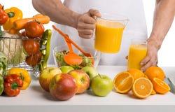 Кашевар руки человека варя cfreshly сжиманный сок на кухне Стоковые Изображения