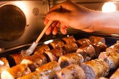 Кашевар смазывая мясо с соусом Стоковое Фото