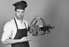 Кашевар с серьезной стороной держит плетеную корзину свежих veggies Стоковое фото RF