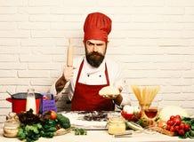 Кашевар с строгой стороной в бургундской форме сидит таблицей с овощами и kitchenware Шеф-повар делает тесто итальянско стоковые фото