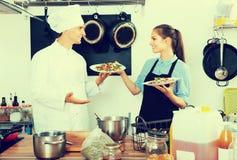 Кашевар человека давая салат к официантке Стоковое Фото