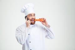 Кашевар шеф-повара говоря на телефоне и есть морковь стоковое фото rf