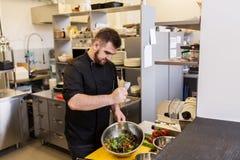 Кашевар шеф-повара делая еду на кухне ресторана Стоковая Фотография