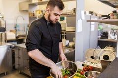 Кашевар шеф-повара делая еду на кухне ресторана Стоковые Фотографии RF