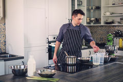 Кашевар шеф-повара работая на современной кухне дома стоковые изображения