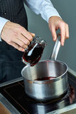 Кашевар льет вино в лоток для варить обдумыванное вино полное собрание кулинарных рецептов Стоковое Изображение RF