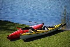2 каяка лежат в лужайке на береге озера, готовом для леев Стоковая Фотография RF