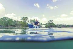 Каякинг на озере, сплавляясь на каяке подводный взгляд молодого человека, разделенная съемка стоковые фото