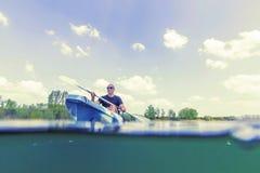 Каякинг на озере, сплавляясь на каяке подводный взгляд молодого человека, разделенная съемка стоковые изображения