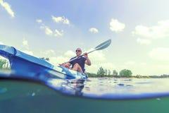 Каякинг на озере, сплавляясь на каяке подводный взгляд молодого человека, разделенная съемка стоковая фотография rf
