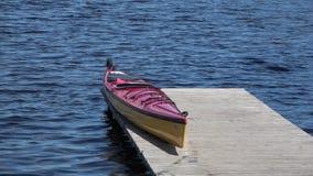Каяк отдыхает на деревянной пристани на озере