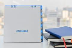 Календарь модель-макета и стог книг Стоковое Изображение