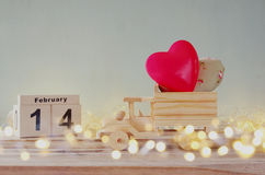 Календарь 14-ое февраля деревянный винтажный с деревянной тележкой игрушки с сердцами перед доской Стоковое Изображение RF