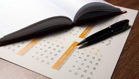 Календарь стены с крупным планом ручки и дневника Стоковые Изображения