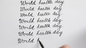 Каллиграфия дня здоровья мира и lattering Девятая линия Взгляд сверху акции видеоматериалы