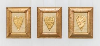 3 кадр сердца золота, белая предпосылка конец вверх Стоковые Изображения