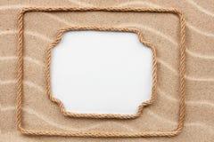 Кадр 2 сделанный веревочки лежа на песке с белой предпосылкой Стоковое Фото