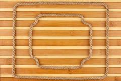 Кадр 2 сделанный веревочки, лож на предпосылке бамбуковой циновки Стоковая Фотография RF