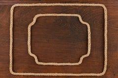 Кадр 2 сделанный веревочки, лож на предпосылке деревянной поверхности Стоковое фото RF