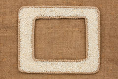 Кадр 2 сделанный веревочки с зернами риса на дерюге Стоковое Изображение RF
