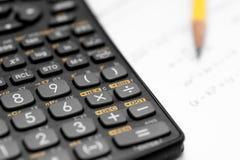 Калькулятор и карандаш на белой предпосылке Стоковое Фото