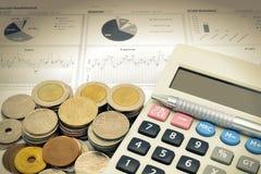 Калькулятор и стог монеток на белой бумаге финансовой диаграммы Стоковые Изображения RF