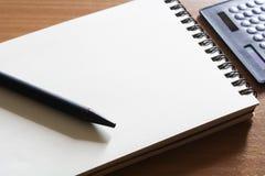 Калькулятор и тетрадь карандаша на деревянном Стоковые Фото