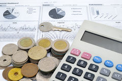Калькулятор, ключ и стог монеток на бумаге финансовой диаграммы Стоковые Изображения