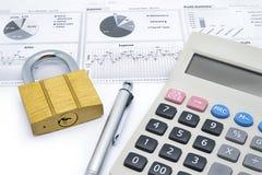 Калькулятор, ручка и ключ для всех замков положенные на финансовую приборную панель Стоковая Фотография