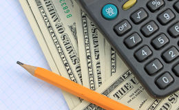Калькулятор, ручка и пусковая площадка на долларах Стоковые Фотографии RF