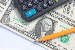 Калькулятор, ручка и пусковая площадка на долларах Стоковые Изображения