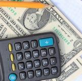 Калькулятор, ручка и пусковая площадка на долларах Стоковое Изображение